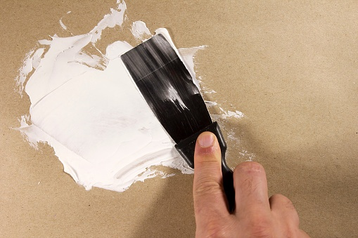 person spackling preparting for painting