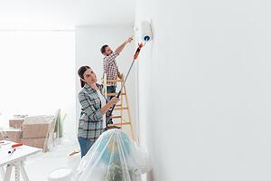couple painting interior of home