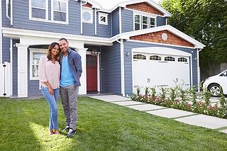 couple standing in front of house