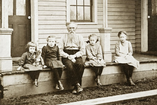 old_portrait_grandpa_sitting_on_porch_with_grandaughters