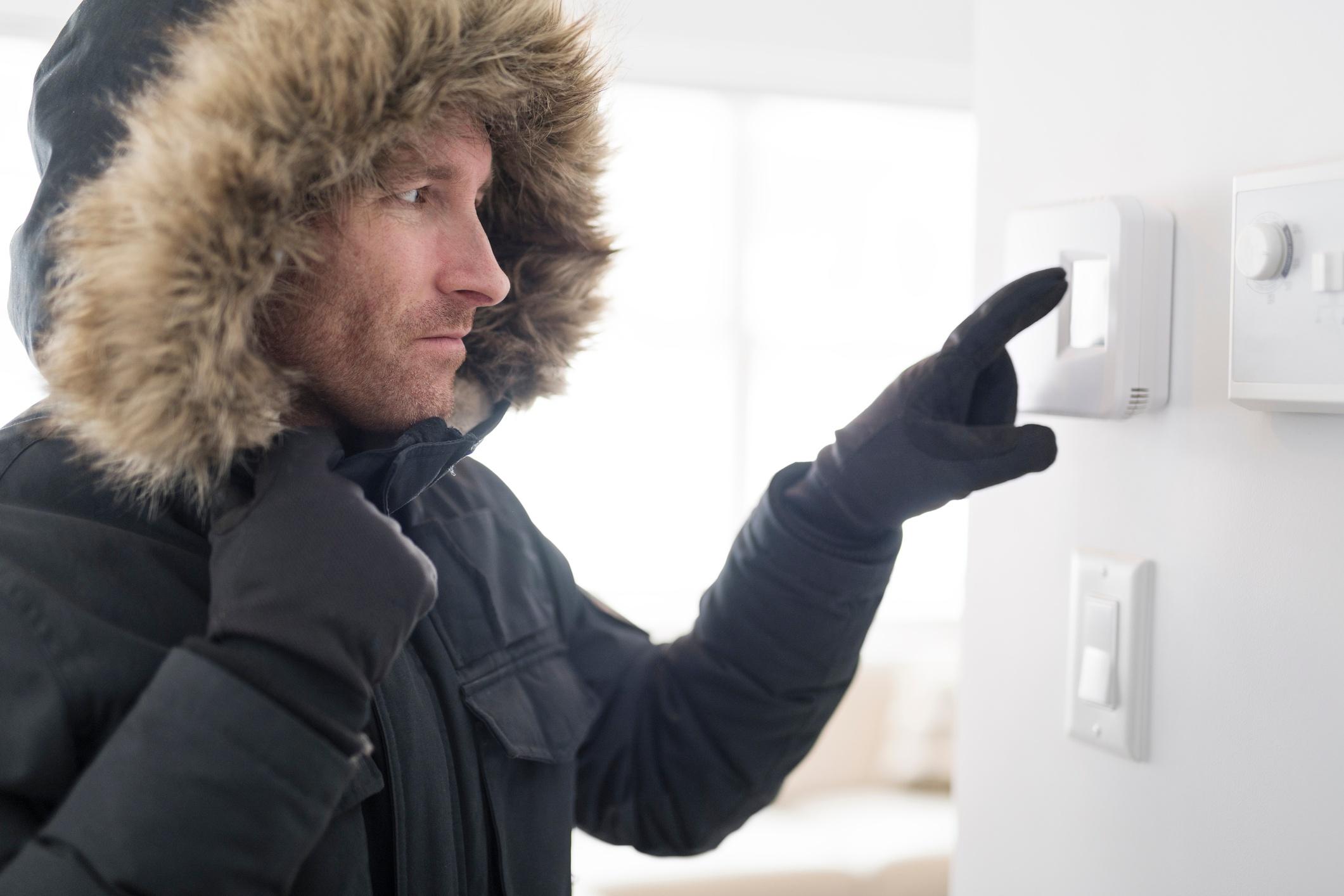 man in parka adjusting thermostat inside his home