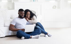 couple looking at house plans on laptop