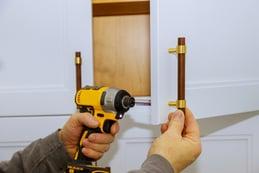 kitchen cabinet hardware being installed